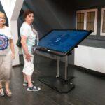 Dwie starsze panie w Cyfrowym Archiwum Historii Iłowej. Jedna z pań stoi przy totemie multimedialnym