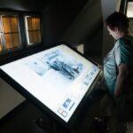 Starsza pani podczas wizyty w Cyfrowym Archiwum Historii Iłowej. Ogląda totem związany z historią