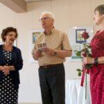 Dwie kobiety i mężczyzna na wystawie malarskiej