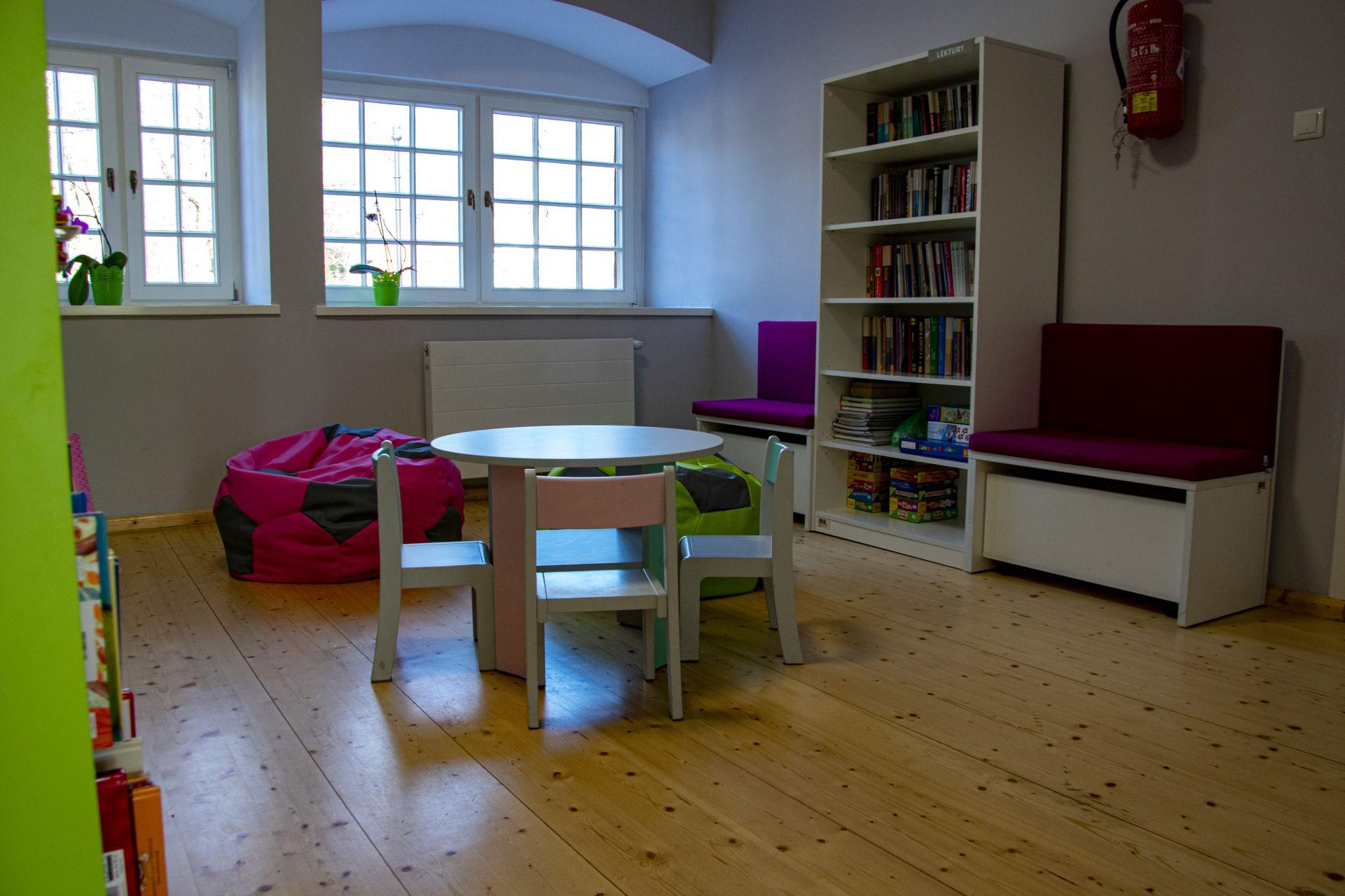 Na środku pokoju stolik z krzesełkami, obok dwie pufu w kształcie piłek na przeciwko stolika regał z książkami, obok ławeczka
