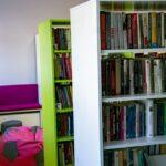 Dwa regały z książkami. Obok pufa do siedzenia w kształcie piłki, dalej ławka z fioletowym obiciem