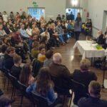 Spotkanie z prof. Bralczykiem. Na sali widać kilkadziesiąt osób, po drugiej stronie profesor siedzi przy stoliku. Obok stoi kobieta z mikrofonem