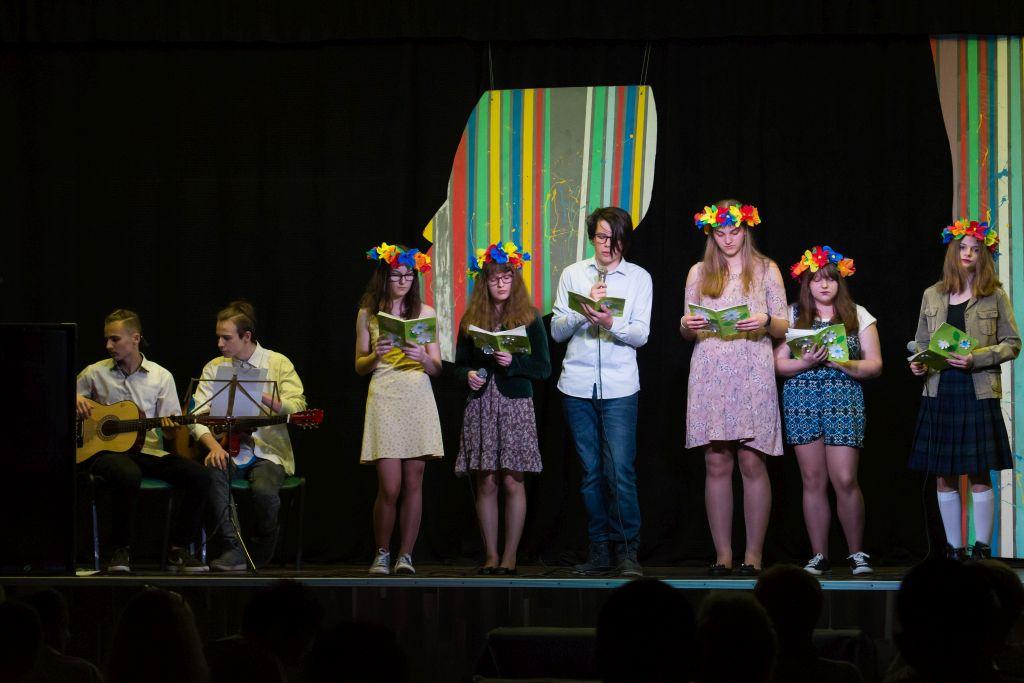 Na scenie grupa dzieci podczas koncertu. Dziewczynki mają kolorowe wianki na głowie. Obok dwaj chłopcy siedzą na krzesłach i grają na gitarach