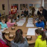 Dzieci podczas warsztatów plastycznych. Zgromadzeni wokół dużego stołu lepią z gliny