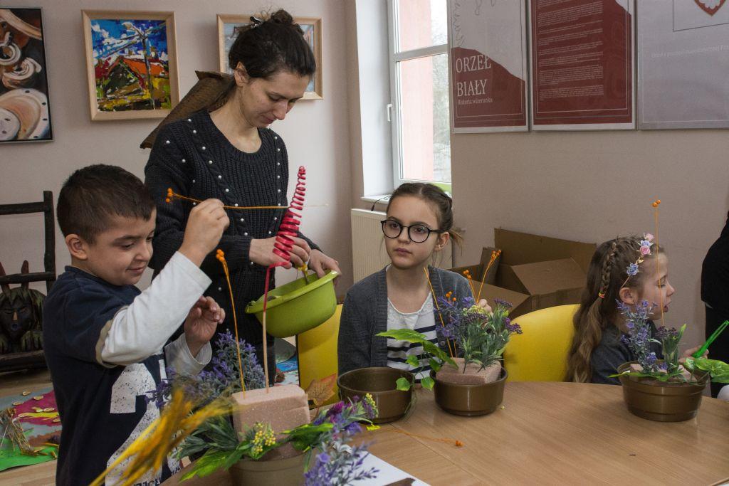 Młoda kobieta, chłopiec i dziewczynka przygotowują kompozycje z kwiatów.