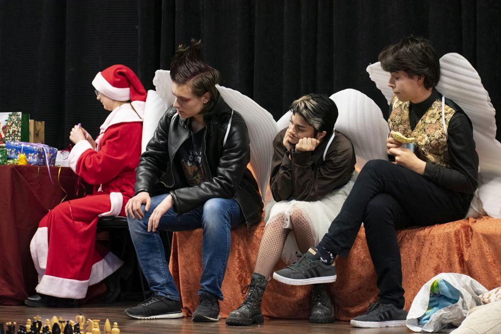 Grupa teatralna podczas występu. Na scenie Mikołaj, który pakuje prezenty i trzech aktorów- siedzą na ławce