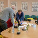 Sekcja fotograficzna podczas zajęć w Bibliotece Kultury w Iłowej. Grupa osób przy stole rozmawia na tematy fotograficzne. Na stole widoczny aparat fotograficzny