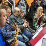 Próba orkiestry. na pierwszym planie pięciu muzyków z instrumentami.Trzy osoby grają na klarnetach, jedna na saksofonie, jedna na flecie poprzecznym