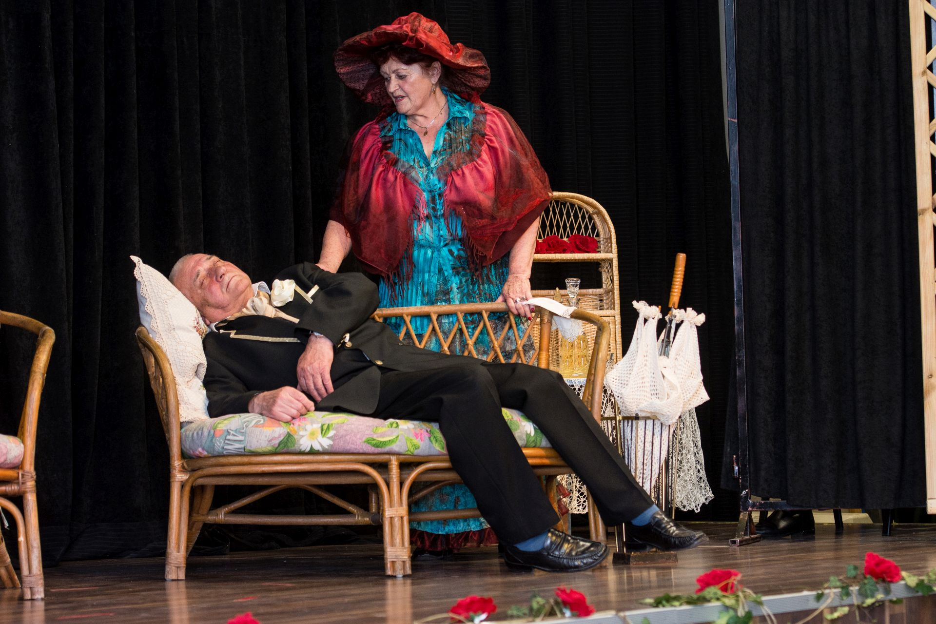 """Teatr """"Oficjalnie bez nazwy"""" podczas występu w Bibliotece Kultury w Iłowej. Na scenie starsza kobieta w czerwonym kapeluszu i pelerynce stoi przy ławeczce na której leży omdlały starszy pan w garniturze"""