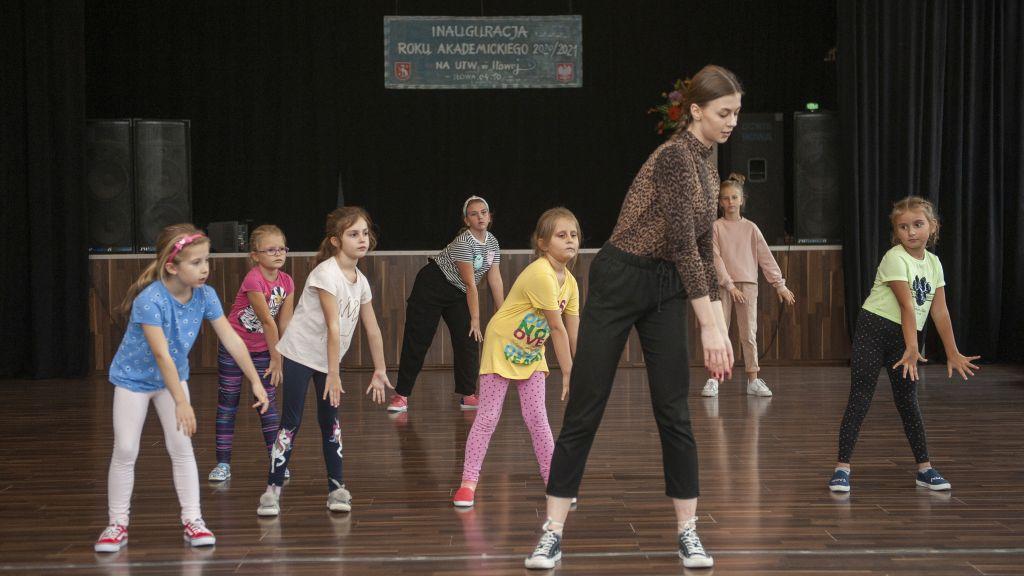 Instruktorka i grupa dzieci podczas występu tanecznego na scenie