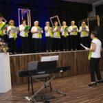 Występ zespołu wokalnego Uniwald. Na scenie 9 kobiet i jedna dyrygentka. Kobiety trzymają w rękach tekst. Śpiewają.