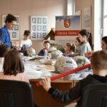 Grupa dzieci zgromadzona wokół stołu podczas wykonywania prac plastycznych. Obok stoi instruktorka