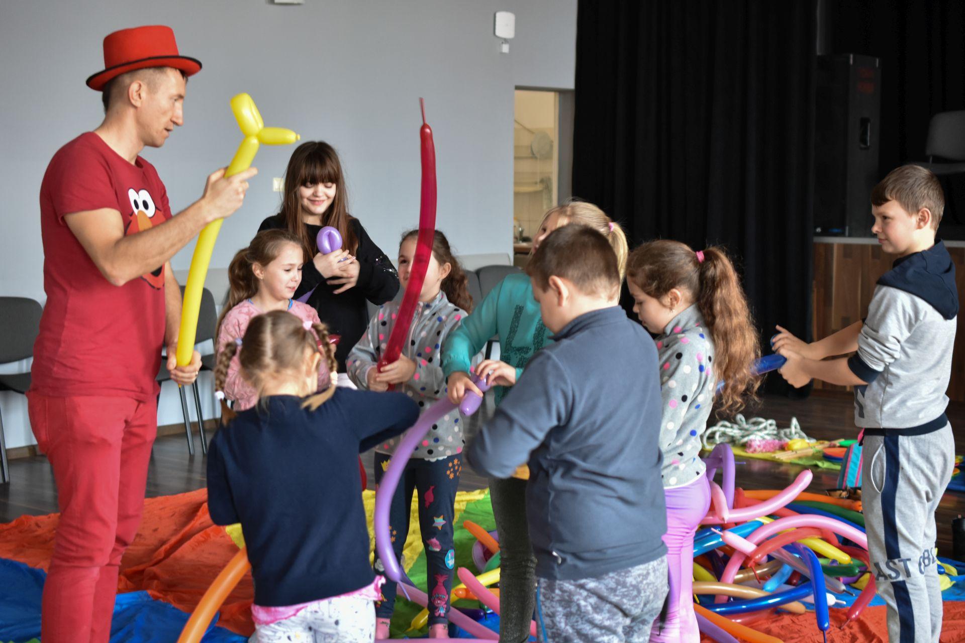 Animator ubrany w czerwoną koszulkę, spodnie i kapelusz oraz grupa rozbawionych dzieci z balonami w rękach