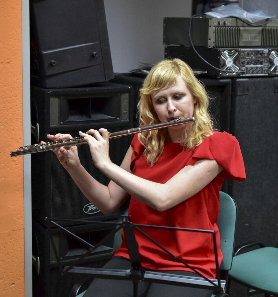 Kobieta siedzi na krześle i gra na flecie poprzecznym. Ubrana jest w czerwona bluzkę i czarne spodnie.