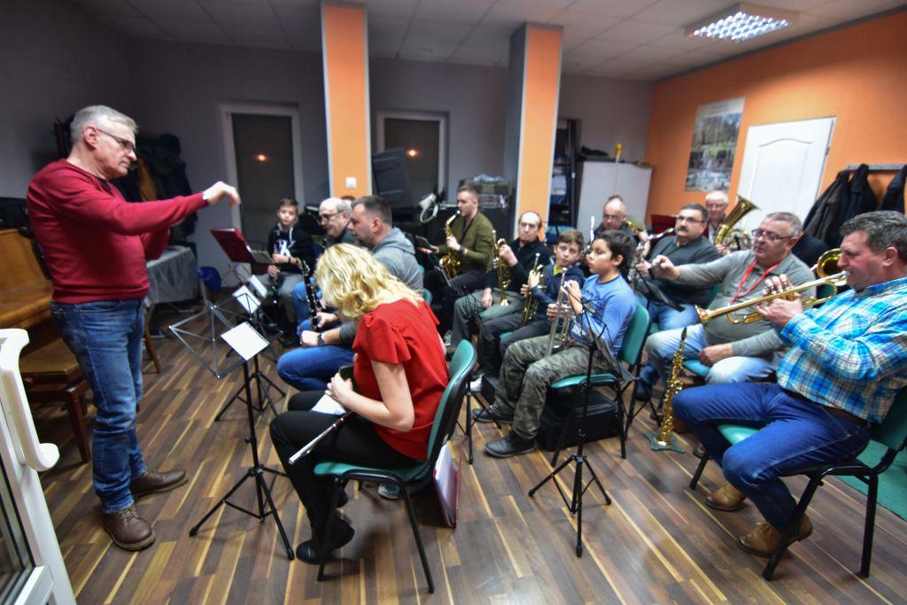 Na pierwszym planie kapelmistrz, dalej grupa muzyków podczas próby orkiestry. Wśród osób widzimy młodzież, dzieci i dorosłych . Wszyscy z instrumentami