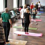 Grupa starszych osób podczas ćwiczeń na sali gimnastycznej. Odwróceni tyłem, stoją wyprostowani na matach