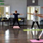 Cztery kobiety odwrócone tyłem podczas ćwiczeń w sali gimnastycznej