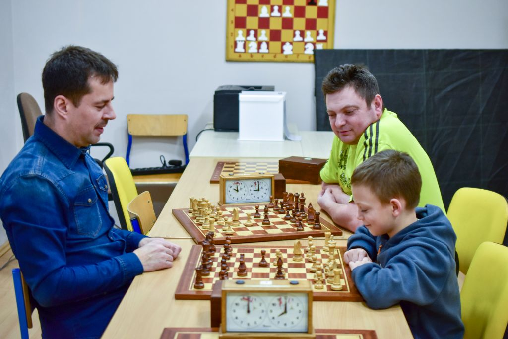 Chłopiec i dwóch panów podczas rozgrywki w szachy