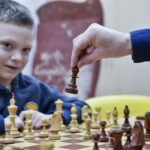 Młody szachista gra w szachy. Patrzy w obiektyw aparatu. Na pierwszym planie dłoń, która trzyma pionek szachowye