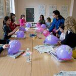 Zajęcia plastyczne. Dzieci siedzą przy stole. Każde z nich ma balon. Obok stoi instruktorka