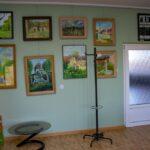 Na ścianach widoczne prace wykonane na płótnie. W pomieszczeniu stoi stolik z krzesłami , sztaluga i stół konferencyjny